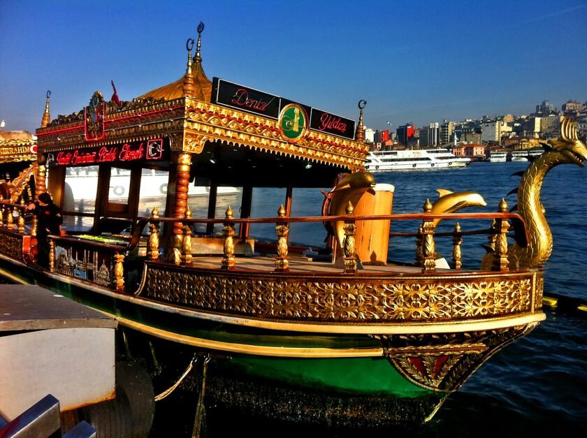 Colorful fishing boats beneath Galata Bridge in Istanbul.