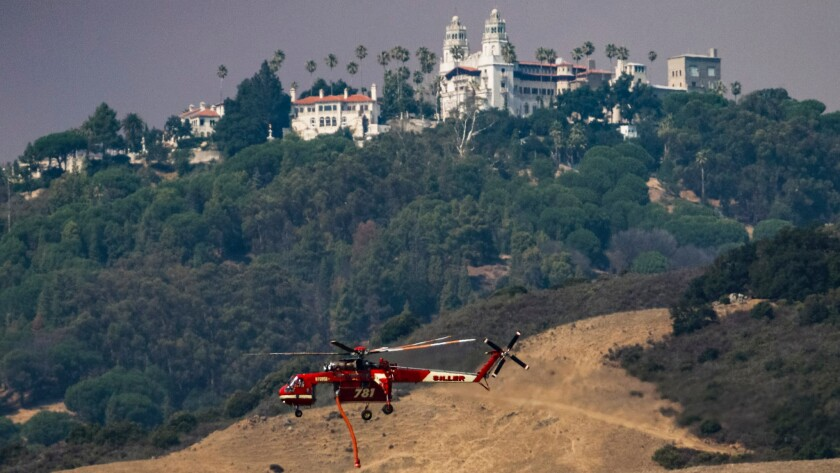 A firefighting helicopter flies past Hearst Castle in San Simeon. The volatile Chimney fire is burning in the area.