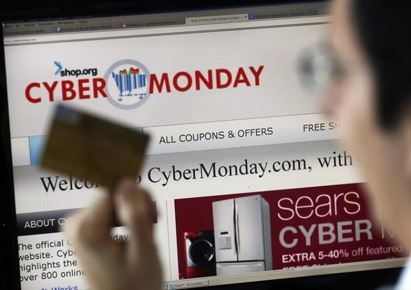 """Fotografía de archivo de un hombre con una tarjeta de crédito frente a un ordenador durante el """"ciberlunes"""". EFE/Archivo"""