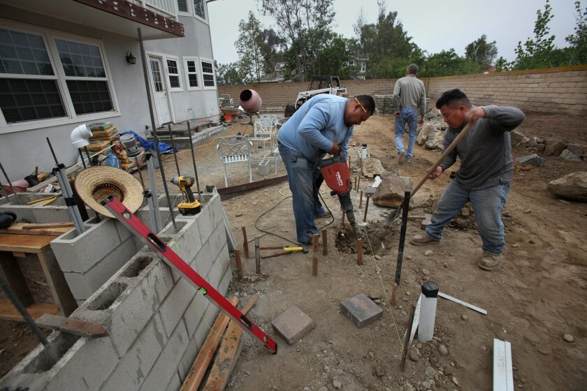 Jose Sanchez, left, and Nicolas Domingo dig in the tough soil where Kathy Woodworth once had a backyard pool. Contractor Tom Teal, background,  designed her new drought-tolerant landscaping.
