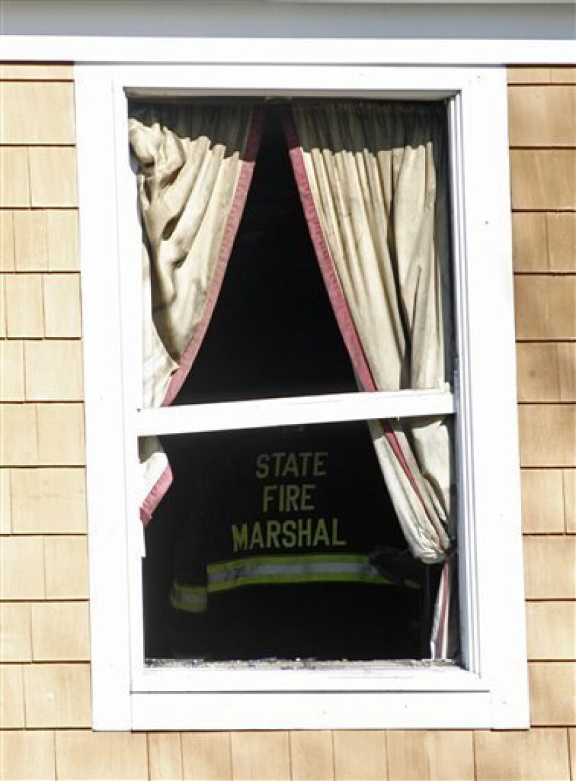 A Rhode Island State fire marshal investigates a home where a fatal fire occurred in Warwick, R.I., Sunday, Feb. 7, 2010. Five people, including a mother and her 7-month-old baby, died in the blaze on Saturday. (AP Photo/Stew Milne)