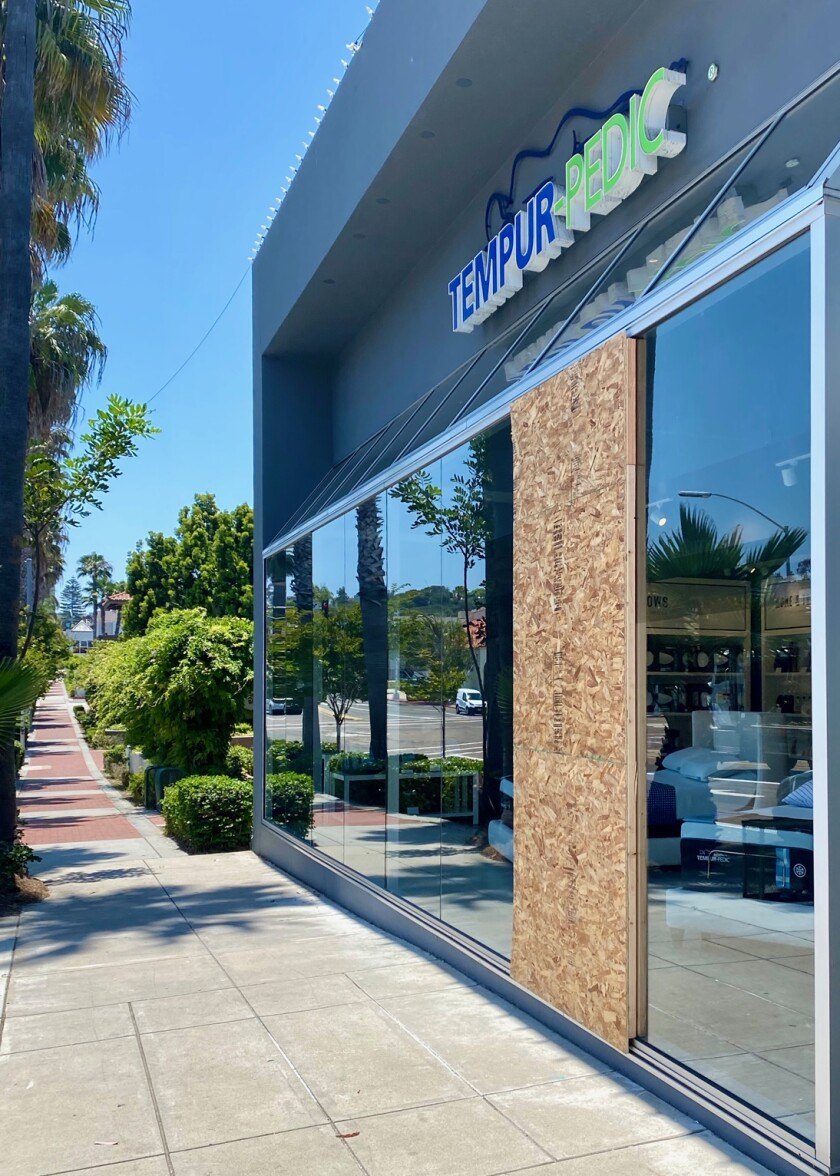A damaged window is boarded up June 3 at the Tempur-Pedic mattress store at 7616 Girard Ave. in La Jolla.