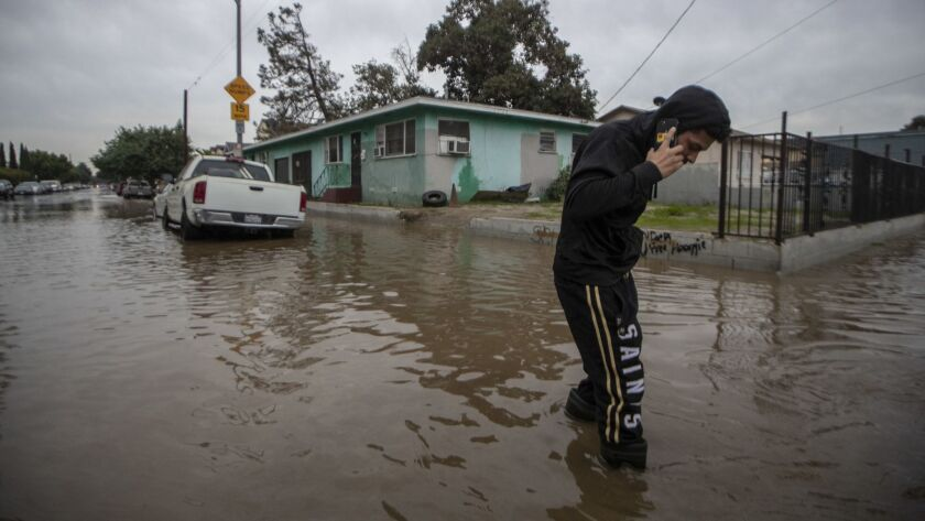 LOS ANGELES, CALIF. -- FRIDAY, DECEMBER 21, 2018: Justin Ibarra crosses a flooded intersectoin at