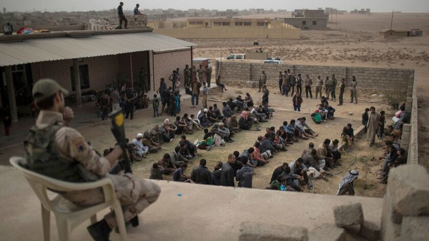 People who fled from Islamic State territory sit Tuesday outside a mosque guarded by Iraqi soldiers in Shuwayrah, south of Mosul.
