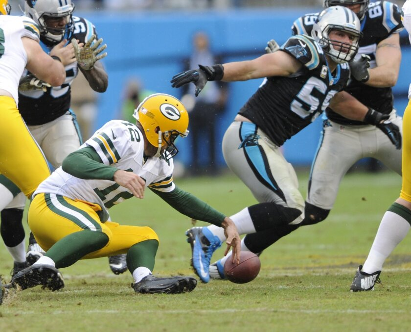 Green Bay Packers' Aaron Rodgers (12) fumbles the ball as Carolina Panthers' Luke Kuechly (59) chases in the second half of an NFL football game in Charlotte, N.C., Sunday, Nov. 8, 2015. Rodgers recovered the ball. (AP Photo/Mike McCarn)
