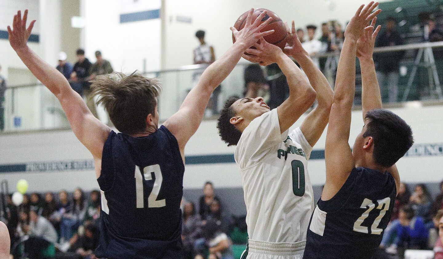 Providence's Jordan Shelley gets to the basket to shoot under defensive pressure from Flintridge Prep's Kevin Ashworth and Zach Kim in a Prep League boys' basketball game at Providence High School auditorium on Tuesday, January 22, 2019.