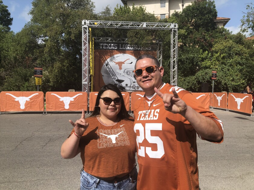 Orlando Candelaria and friend Evelyn Salcedo gesture horn signs while wearing Longhorns shirts.
