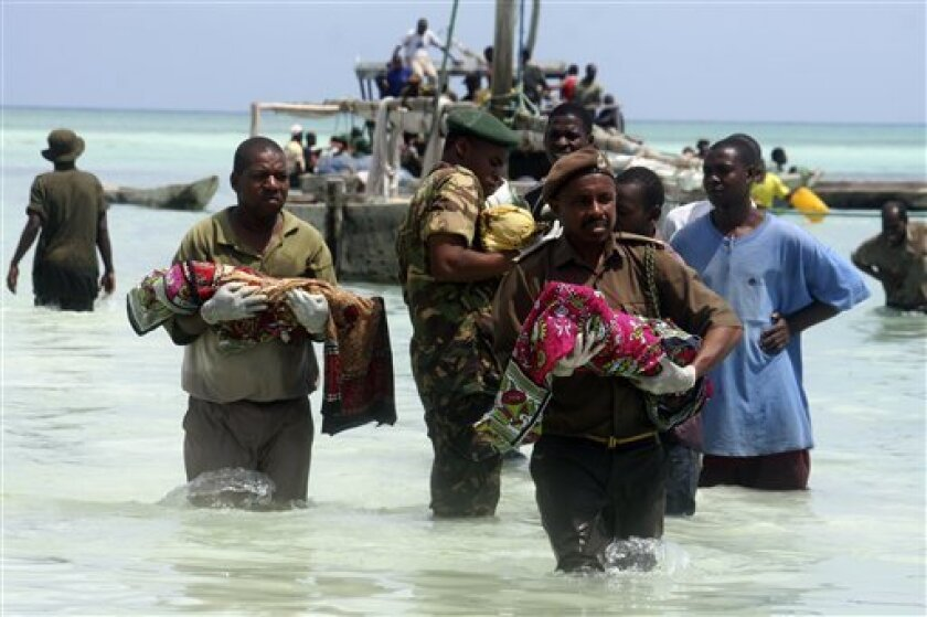 CORRECTING PHOTOGRAPHER BYLINE TO ALI SULTAN - Tanzanian police carry bodies of children from the sea in Zanzibar, Tanzania, Saturday Sept 10, 2011. An overcrowded ship sank in deep sea off mainland Tanzania on Saturday with about 600 people onboard, and about 370 people are believed missing or dead. The ferry, M.V. Spice Islanders, was heavily overloaded and some potential passengers had refused to board when it was leaving the mainland port of Dar es Salaam, said survivor Abdullah Saied. It sank in an area with heavy currents in deep sea between mainland Tanzania and Pemba Island at about 1 a.m. Saturday. About 230 people had been rescued and 40 bodies had been recovered, said Mohamed Aboud, the minister for the vice president's office. (AP Photo/Ali Sultan)