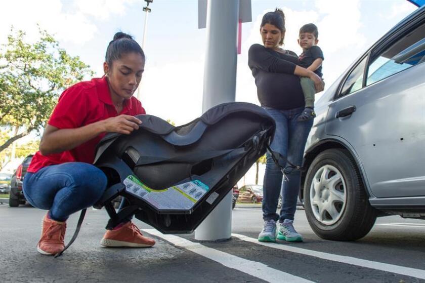 Isley More (d) carga su hijo Miguel Ángel Rincón mientras sigue las orientaciones de la instructora certificada en Seguridad de Pasajeros Infantiles, Tatiana Pozo (i), durante un evento sobre seguridad en los asientos de niños. EFE/Archivo