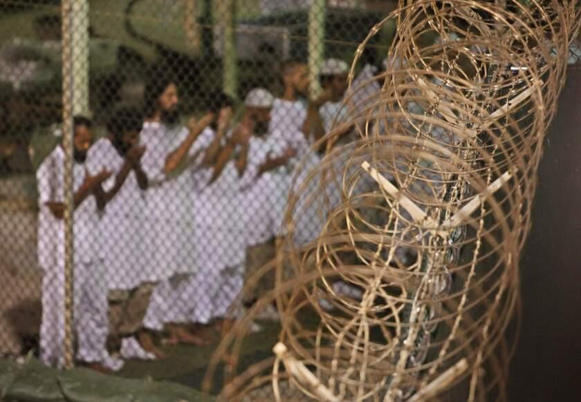 Guantanamo detainees pray before dawn near a fence of razor-wire, inside Camp 4 detention facility at Guantanamo Bay U.S. Naval Base, Cuba.