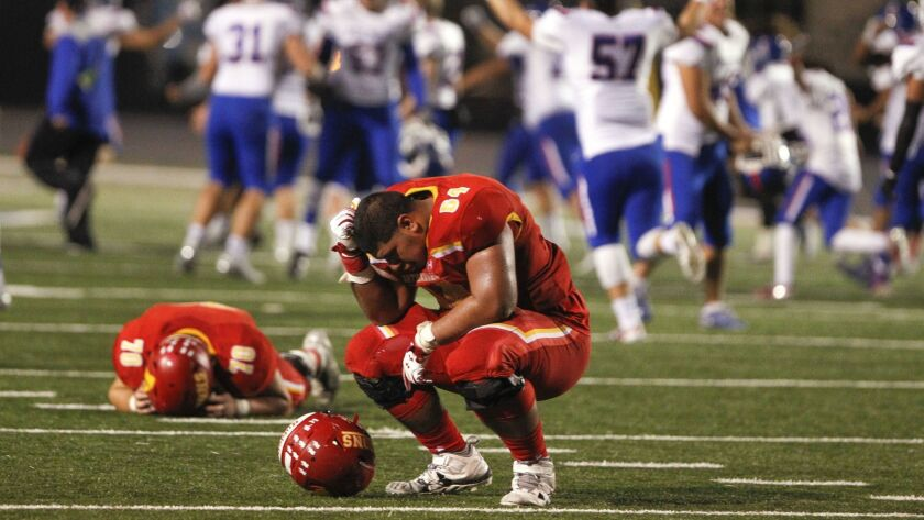 Cathedral Catholic's Ross Ulugalu-Maseuli (right) and Trenton Quick take the loss hard as Folsom celebrates its 21-14 overtime win.