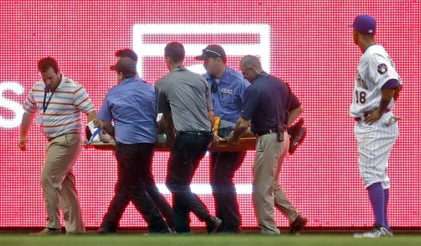 Milwaukee Brewers left fielder Khris Davis watches as a fan is helped off the field during the eighth inning of a baseball game against the Minnesota Twins Tuesday, June 3, 2014, in Milwaukee. The fan fell from the seats into the bullpen and was injured in the fall. (AP Photo/Morry Gash)
