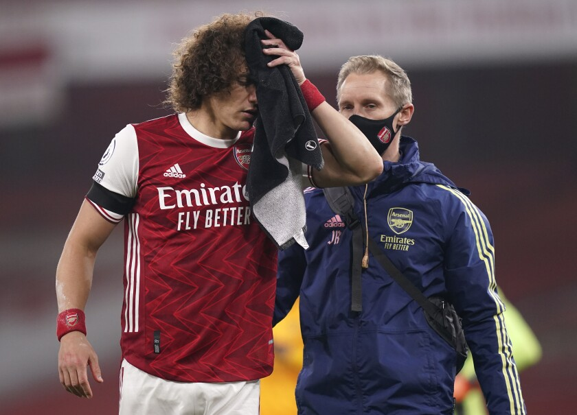 Arsenal's David Luiz holds a towel on a cut to his head following a clash with Wolverhampton Wanderers' Raul Jimenez during the English Premier League soccer match between Arsenal and Wolverhampton Wanderers at Emirates Stadium, London, Sunday, Nov. 29, 2020. (John Walton/Pool via AP)