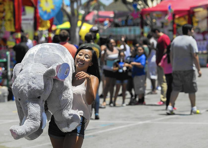 In this 2014 photo, Sia Keys carries a giant stuffed elephant that she won in the ring toss during the Orange County Fair in Costa Mesa. The fair board voted unanimously Monday to cancel the 2020 fair in light of the coronavirus.