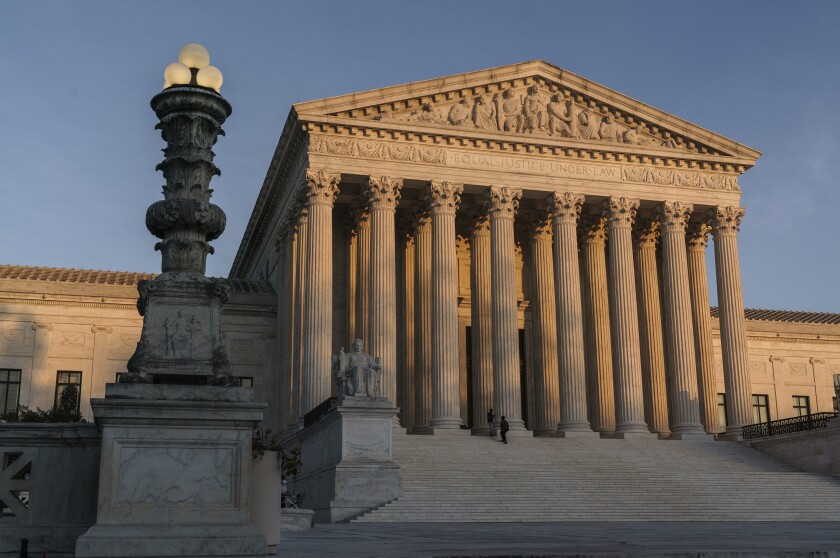 FILE - In this Nov. 6, 2020, file photo the Supreme Court is seen as sundown in Washington. The Supreme Court says it will continue to hear arguments by telephone through at least January because of the coronavirus pandemic. The court's announcement Wednesday, Nov. 25, extends telephone arguments by a month. (AP Photo/J. Scott Applewhite, File)