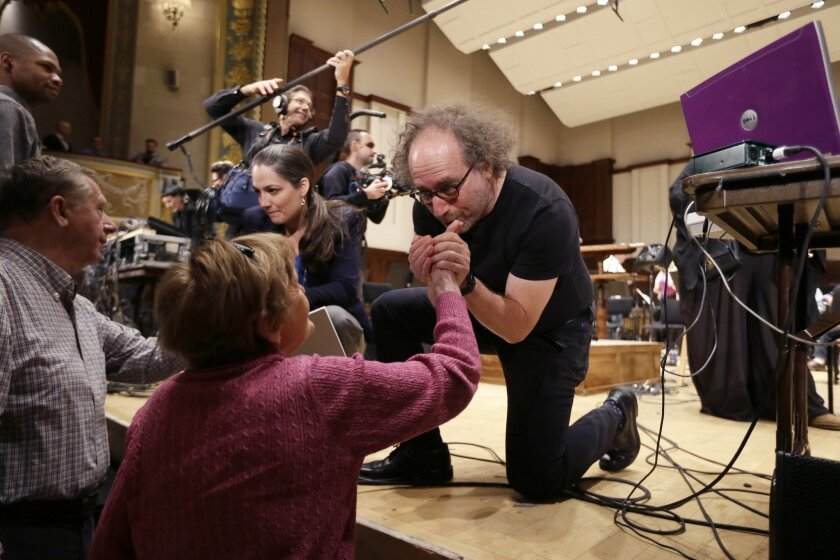 """Massachusetts Institute of Technology professor Tod Machover greets supporters after a rehearsal at the Detroit Symphony Orchestra, Thursday, Nov. 19, 2015, in Detroit. The DSO has teamed up with the international composer to create an original musical work designed to answer the question: """"What does Detroit sound like?"""" The result is """"Symphony in D,"""" a blend of melodies played by traditional orchestral instruments combined with everyday Detroit sounds collected, digitized, and translated into music via software developed by Machover. (AP Photo/Carlos Osorio)"""