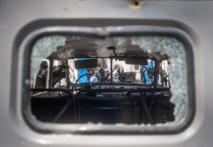 A police car window shattered in a nighttime attack on a Ukraine national guard post in Mariupol.