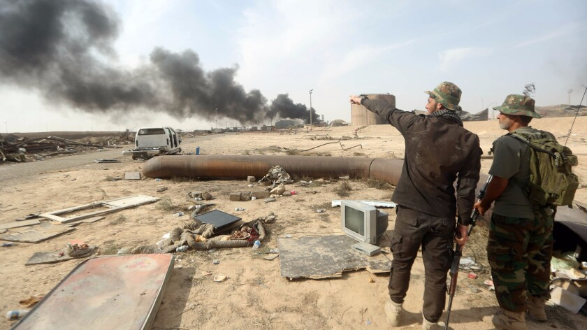 Iraqi fighters look at the damage Oct. 17, 2015, after security and allied paramilitary forces recaptured a refinery complex from Islamic State extremists in Baiji.