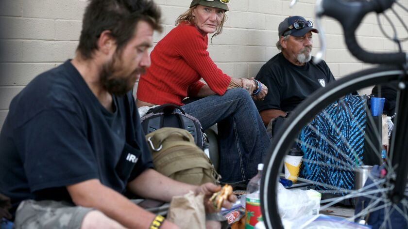 From left, Daniel Seavello, Traci Deeks, and her husband, Lee Deeks, sit among their possessions after they had gathered food and toiletries during an event staged by a group of activists who gathered to feed the homeless at Wells Park in El Cajon in November 2017.
