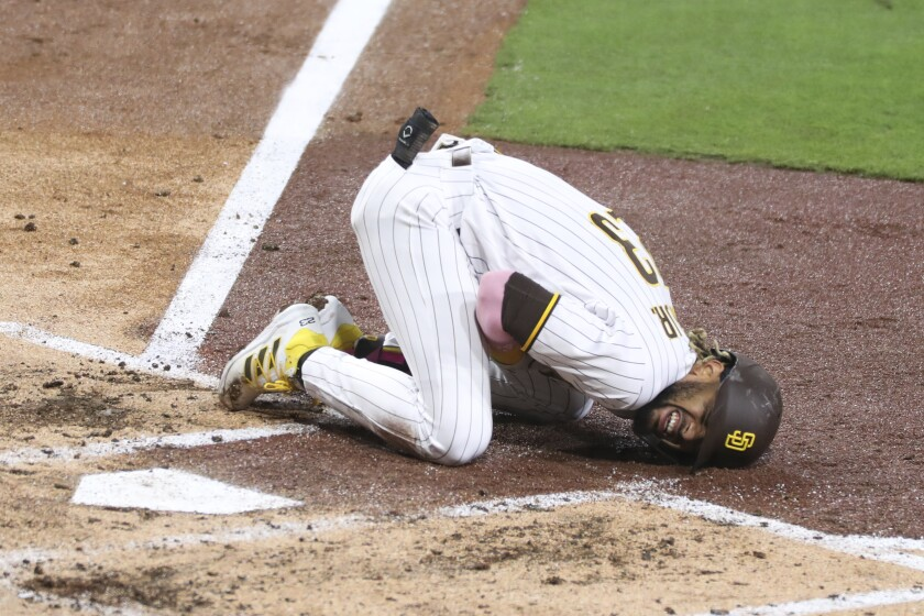 San Diego Padres' Fernando Tatis Jr. reacts after hurting his shoulder while swinging at a pitch in the third inning of a baseball game against the San Francisco Giants, Monday, April 5, 2021, in San Diego. (AP Photo/Derrick Tuskan)