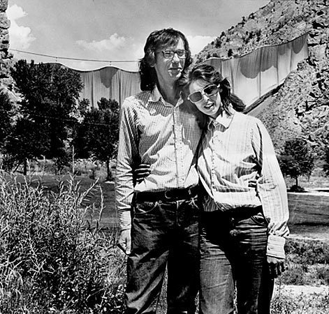 """Christo and his wife, Jeanne-Claude, stand in front of their concept art project, """"Valley Curtain,"""" in 1972."""
