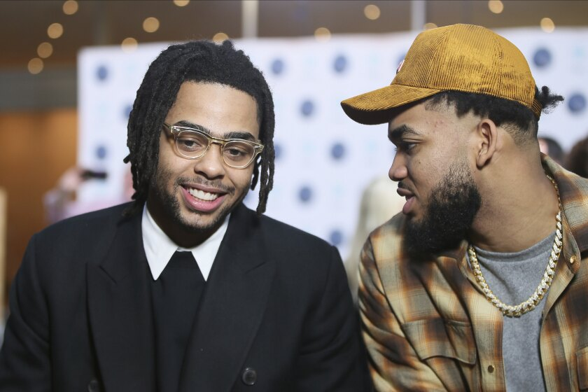 New Minnesota Timberwolves NBA basketball player D'Angelo Russell, left, chats with Timberwolves' Karl-Anthony Towns after Russell was introduced at a news conference, Friday, Feb. 7, 2020, in Minneapolis, following a trade that sent Timberwolves' Andrew Wiggins to the Golden State Warriors. (AP Photo/Jim Mone)