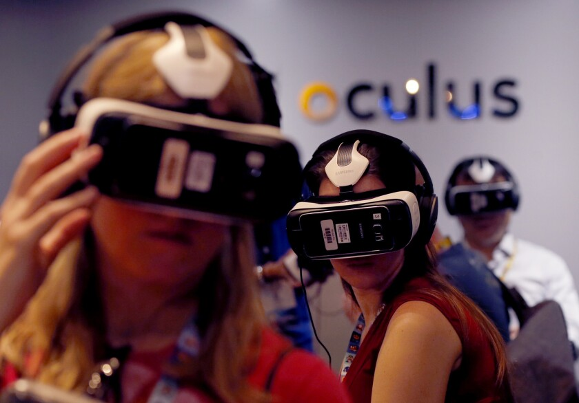 Video game enthusiasts try out the Samsung VR powered by Oculus virtual reality goggles at the E3 annual video game conference in Los Angeles on June 16.