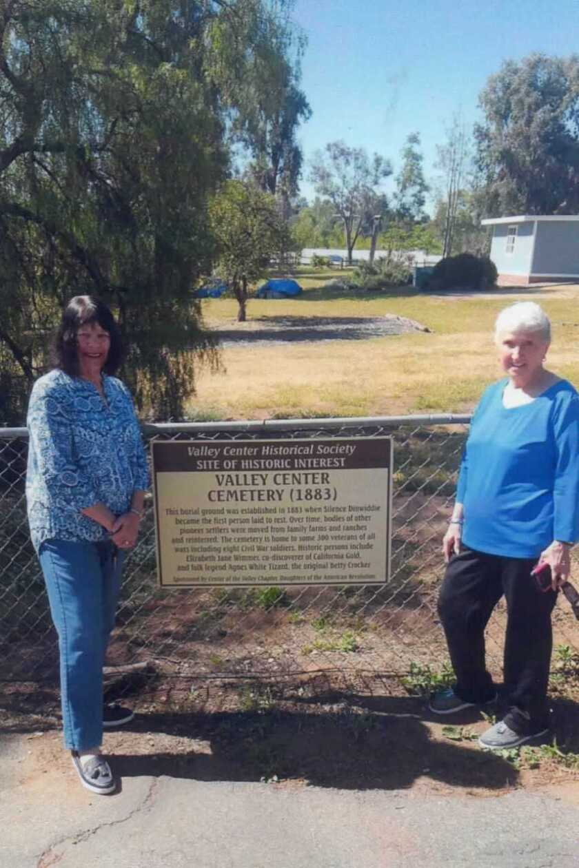 The latest in a series of signs marking local historic sites has been mounted at Valley Center Cemetery, which dates back to 1883. The Valley Center Historical Society began the process of marking historic places in 2010 and has identified more than a dozen. Shown at the most recent installation are Sharon Healey Bartholomew (left), regent of the Center of the Valley chapter of Daughters of the American Revolution, and Louise Kelly, president of the Cemetery District. The Valley Center DAR chapter sponsored the cemetery sign on behalf of the Historical Society.
