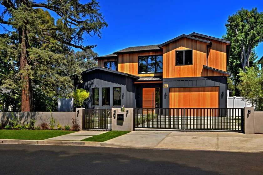 The newly built home, listed for $3.195 million, stands out from neighboring Farmhouse-inspired homes with rich cedar and black-hued siding. Inside, clapboard siding and light oak floors enhance the open floor plan of nearly 5,200 square feet. Pocketing walls of glass open the common area to the backyard and swimming pool. A master suite with a fireplace and private balcony is among six bedrooms and eight bathrooms. There's also an office. Outside, lawn surrounds a newly added swimming pool and spa. Nearby are a pool house, a built-in barbecue and lounge areas.
