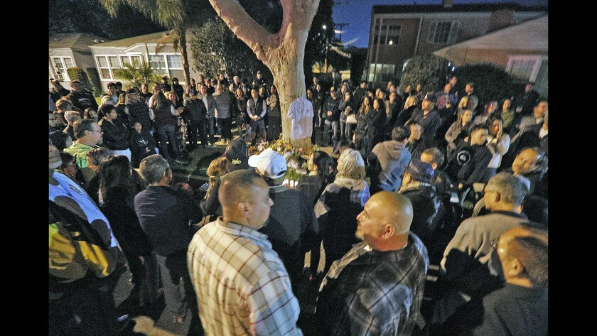 """A large circle of people that spread onto the second lane of Alamada Avenue surrounds a shrine for fallen friend and bicyclist Lenny Trinh on the 1300 block of Alameda Avenue in Burbank on Wednesday, April 18, 2018. This is the location where Lenny Trinh was killed on his bicycle earlier in the week. Over 100 people, mostly family and friends with some who paid tribute but didn't know him, told stories, and chained a """"ghost bike"""" to a tree."""