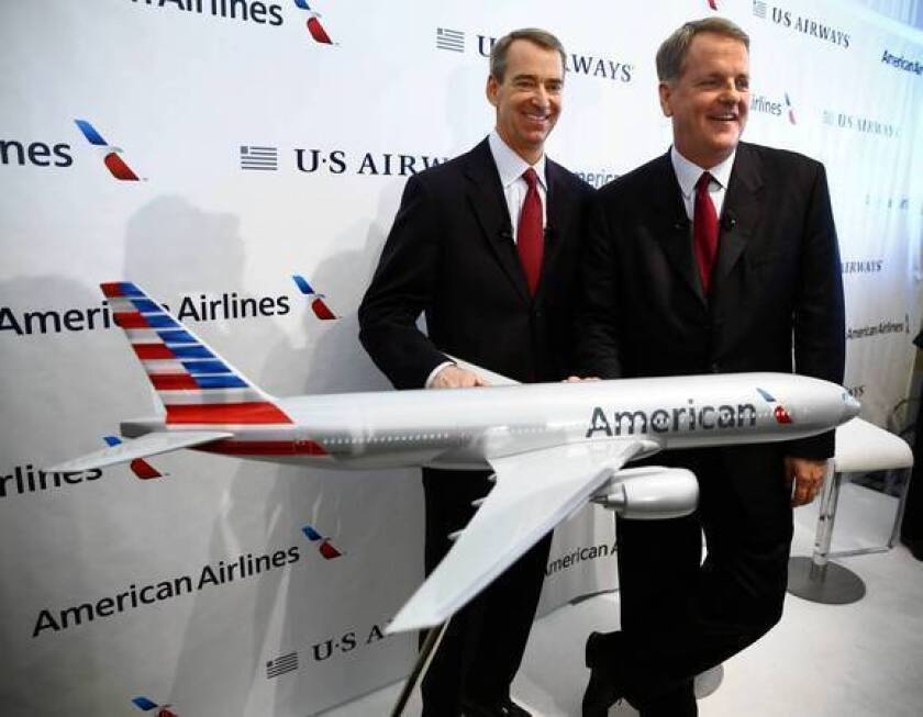 American Airlines CEO Tom Horton, left, and US Airways CEO Doug Parker appear with an airplane model bearing the new American Airlines logo after announcing the two airlines' merger at Dallas-Fort Worth International Airport.