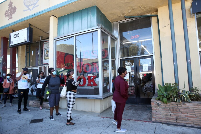 Customers wait in line to enter Eso Won Books in Leimert Park on Saturday, Nov. 28.