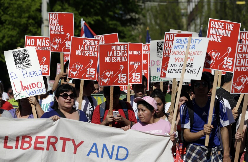 Hundreds of demonstrators walk toward downtown Seattle during a May Day march, some carrying signs in support of a boost in the minimum wage.