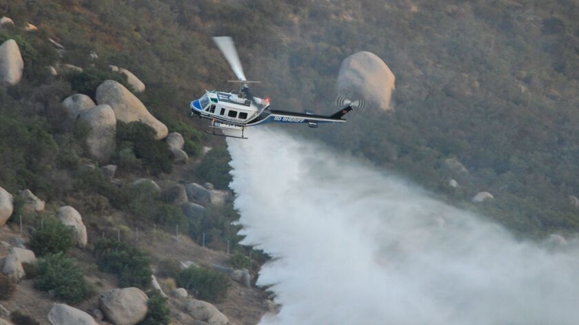 A sheriff's helicopter dumps water on flames above Wildcat Canyon Road north of Lakeside Saturday.