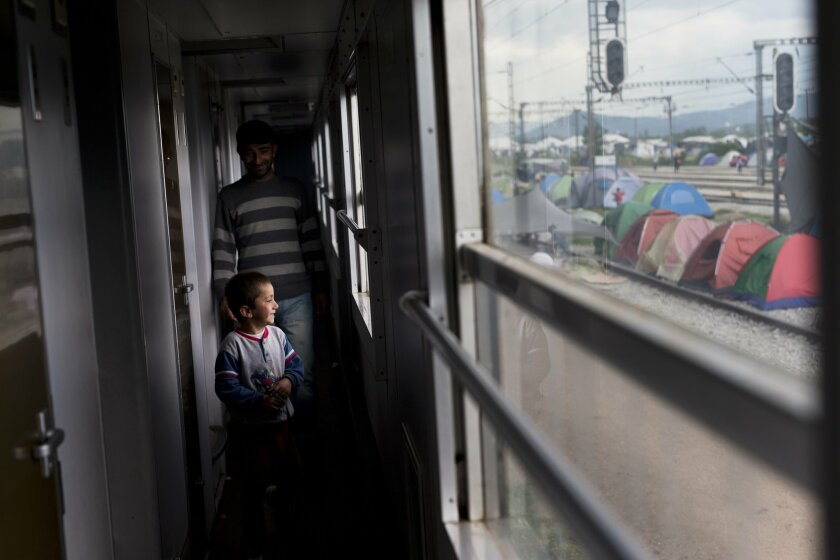 In this Saturday, May 7, 2016 photo, a man walks with his child inside a train as tents are seen outside  in the sprawling refugee and migrant tent city of Idomeni, on Greece's northern border with Macedonia. (AP Photo/Petros Giannakouris)