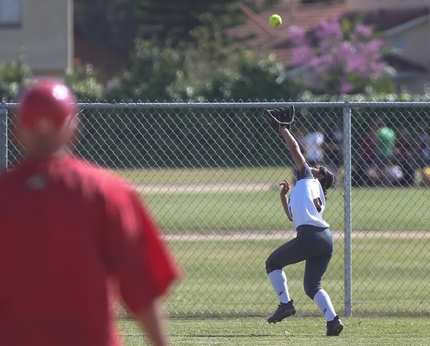 Los Amigos left fielder Leslie Lopez reaches for a deep fly ball during Garden Grove League girls' s