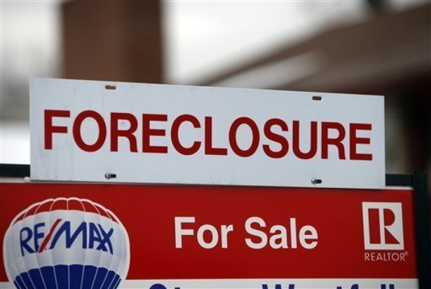 A foreclosure sign sits on top of a sale placard outside a home on the market in the south Denver suburb of Littleton, Colo., on Tuesday, Dec. 23, 2008. To those on the front lines of the housing crisis, the Obama administration's plan to spend $50 billion to combat foreclosures was a welcome change in the government's approach. But the plan won't be unveiled for at least a week and might not be enough to prevent the housing market's troubles from mushrooming further. (AP Photo/David Zalubowski)
