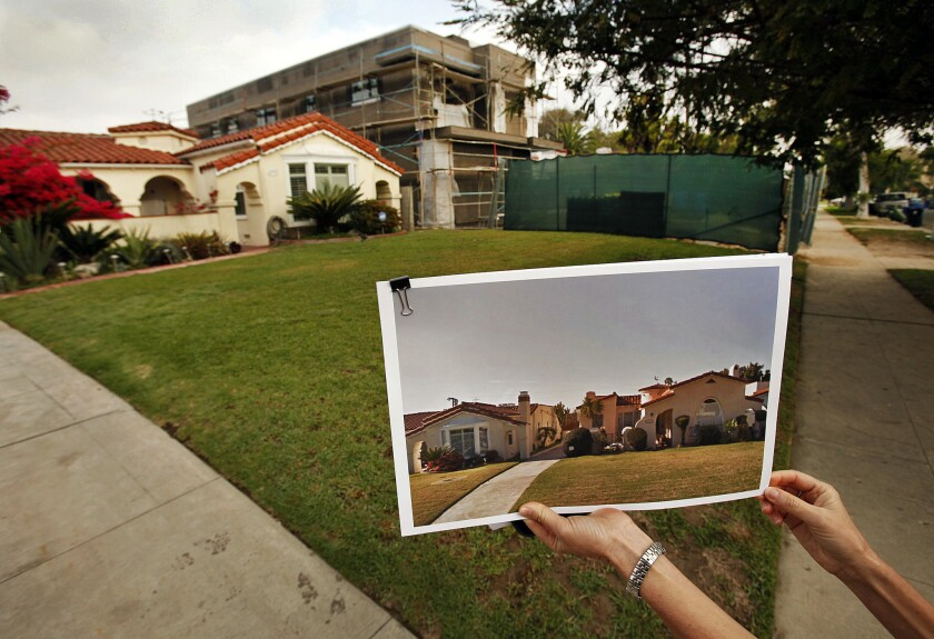 """Traci Considine shows a """"before"""" photo of a home under construction in her Faircrest Heights neighborhood in Los Angeles on March 14, 2014."""