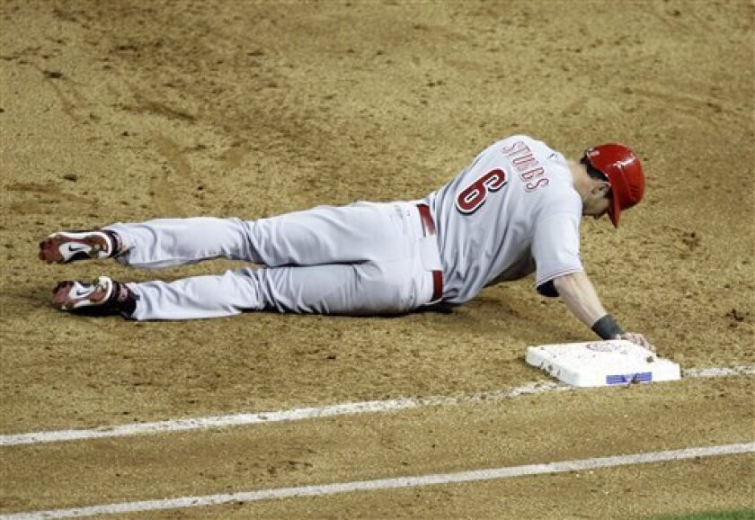 Cincinnati Reds' Drew Stubbs cluthces first base after being picked off by Arizona Diamondbacks pitcher Ian Kennedy in the fifth inning of an MLB baseball game, on Opening Day for the Diaondbacks Friday, April 8, 2011, in Phoenix. (AP Photo/Paul Connors)