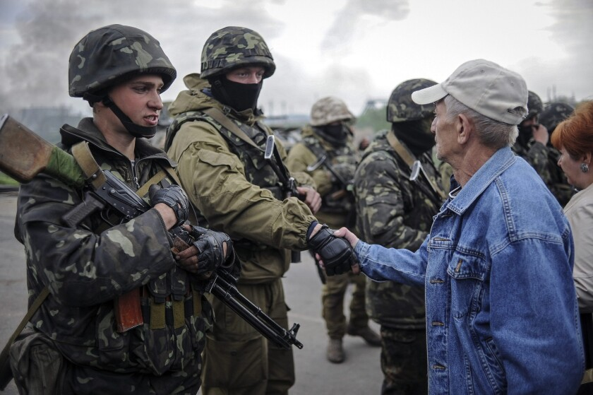 A resident speaks with Ukrainian soldiers near a checkpoint that they seized not far from Slovyansk.