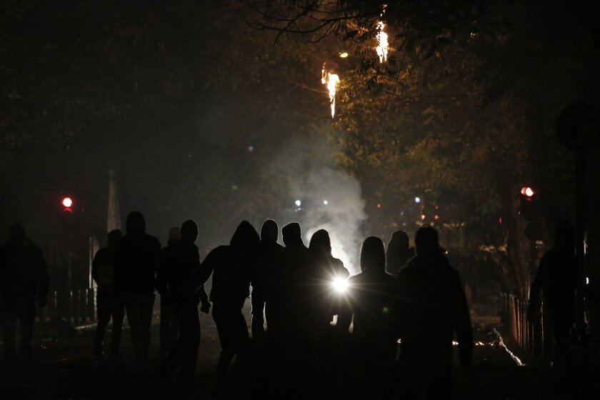 Protesters are silhouetted by the lights of a water canon during riots in Athens neighborhood of Exarchia, a haven for extreme leftists and anarchists, on Saturday, Dec. 6, 2014. A march through central Athens to mark the sixth anniversary of the fatal police shooting of an unarmed teenager quickly