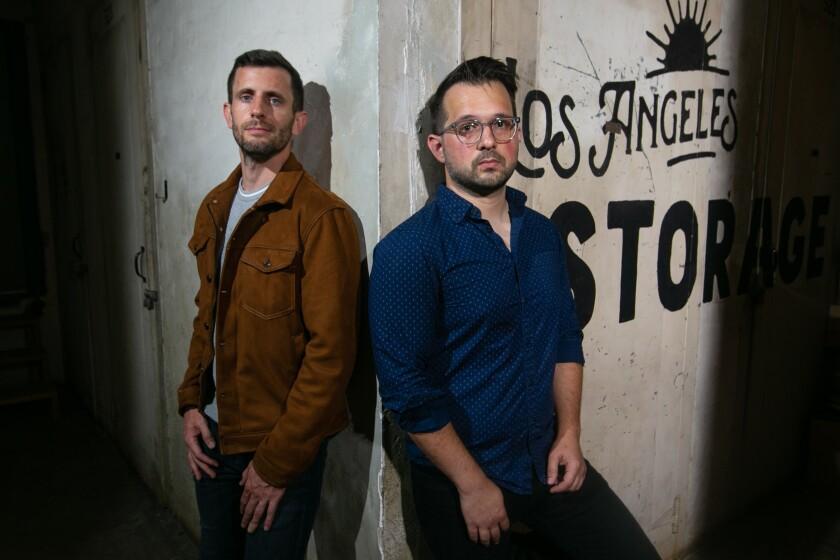 """Dos hombres están apoyados contra una pared con la inscripción """"Almacén de los Ángeles"""""""