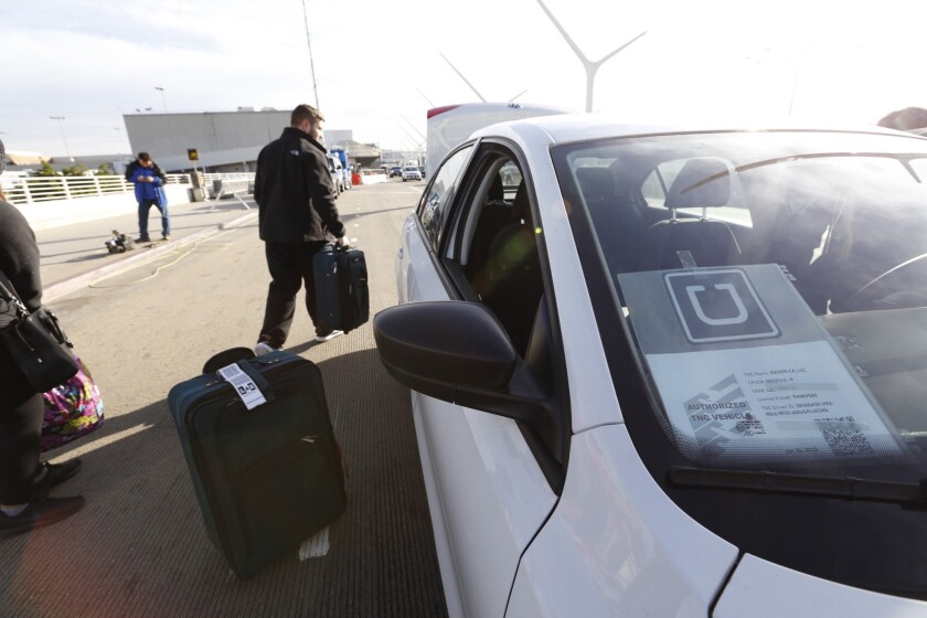 A passenger loads his suitcase into his UberX ride at Los Angeles International Airport.