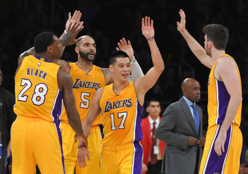 Los Angeles Lakers players Tarik Black (#28), Carlos Boozer (#5), Jeremy Lin (#17) and Ryan Kelly celebrate the victory over the Orlando Magic.