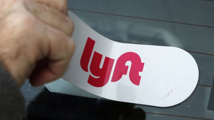 FILE - In this Jan. 31, 2018, file photo, a Lyft logo is installed on a Lyft driver's car in Pittsbu