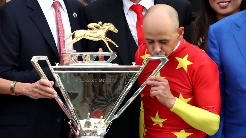 Jockey Mike Smith kisses the Triple Crown Trophy after the 150th running of the Belmont Stakes at Belmont Park on Saturday.