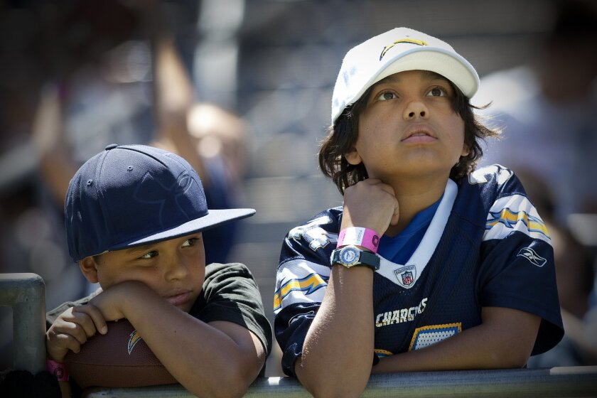 At Chargers Fan Fest at Qualcomm Stadium, Andrew Hernandez, 8, and his brother Anthony Hernandez, 11,  patiently wait for the end of practice so they can get autographs.