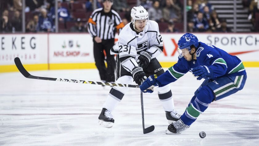 Los Angeles Kings' Dustin Brown (23) passes the puck past Vancouver Canucks' Michael Del Zotto (4) d