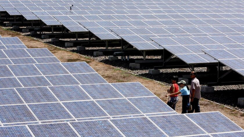 In this 2007 photo, tourists walk past solar panels at the photovoltaic premises of Cagayan Electric Power and Light Co. in the southern Philippines.