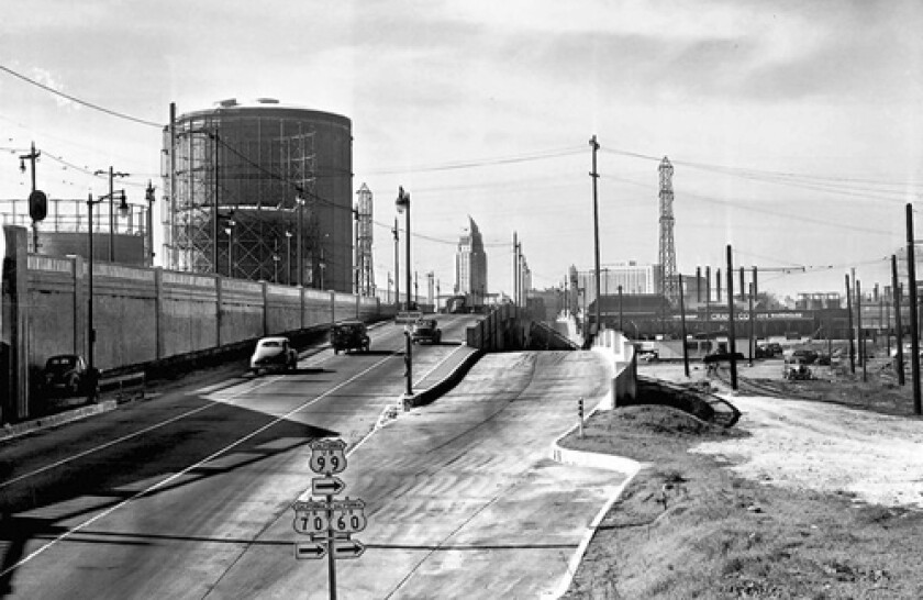 This general view shows motorists arriving from the east along U.S. Highway 99-70 or 60, as they enter Los Angeles on May 30, 1947. The Los Angeles City Hall tower is the tall building left of the left lane, and the post office is right of the right lane.